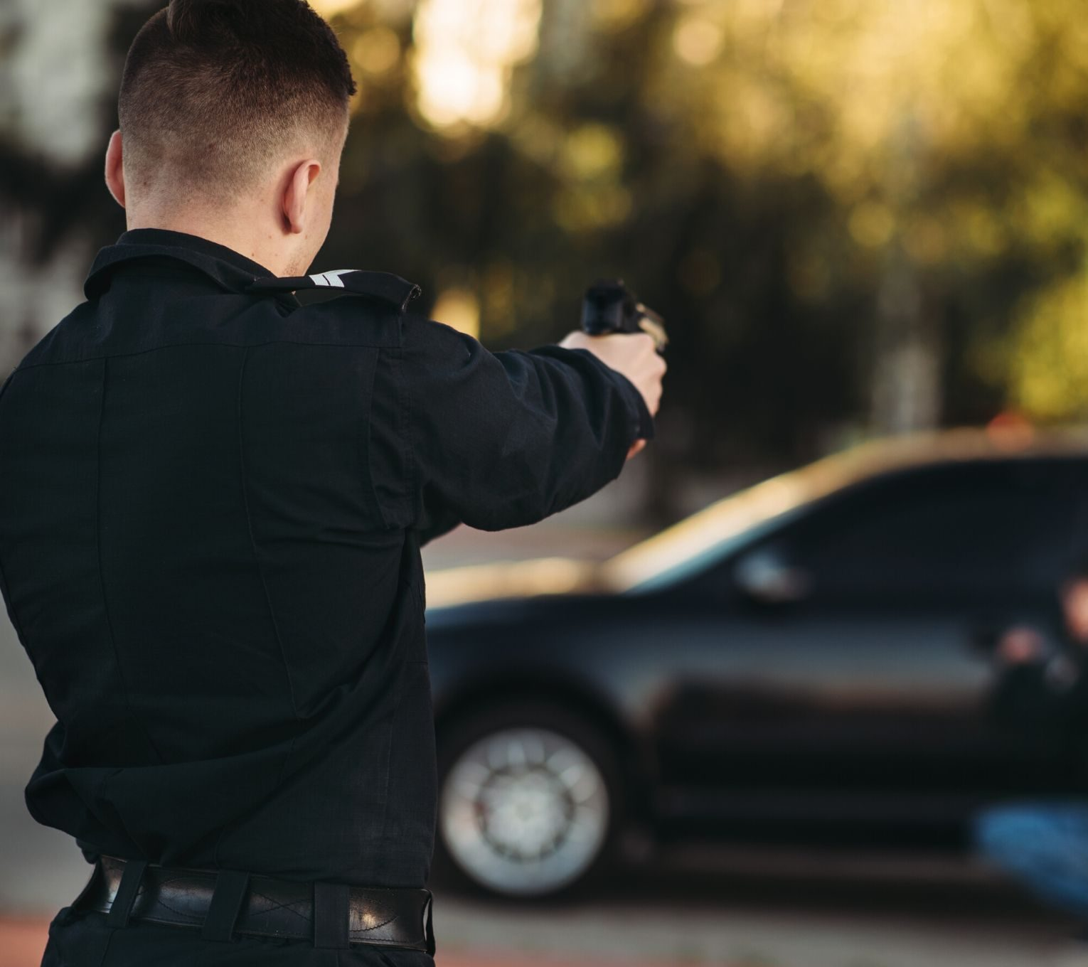 a police officer pointing a gun at someone